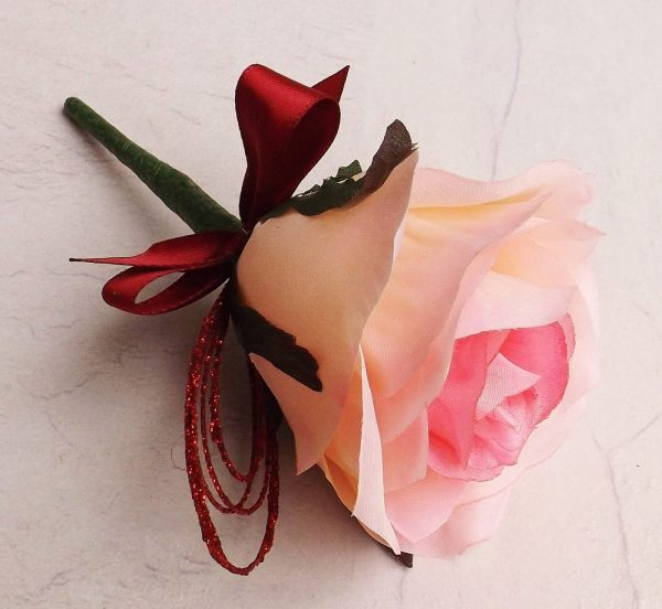 A silk pink rose buttonhole with burgundy glitter loop, burgundy ribbon