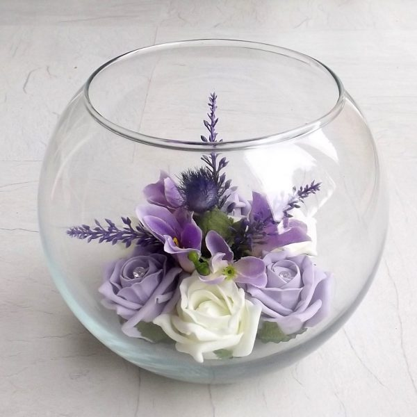 A fishbowl centrepiece with lilac foam roses, thistles, lilac and roses