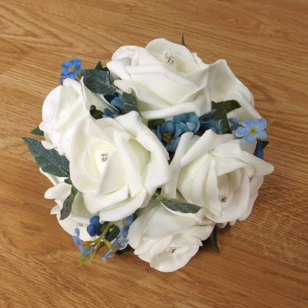 An ivory foam rose and forget me not cake topper