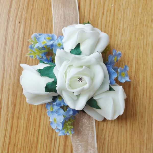 An ivory foam rose and forget me not wrist corsage