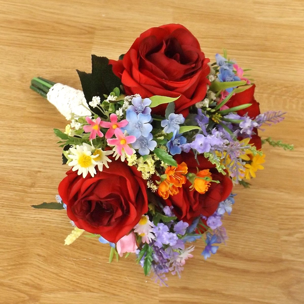 A silk red rose and wildflower brides bouquet